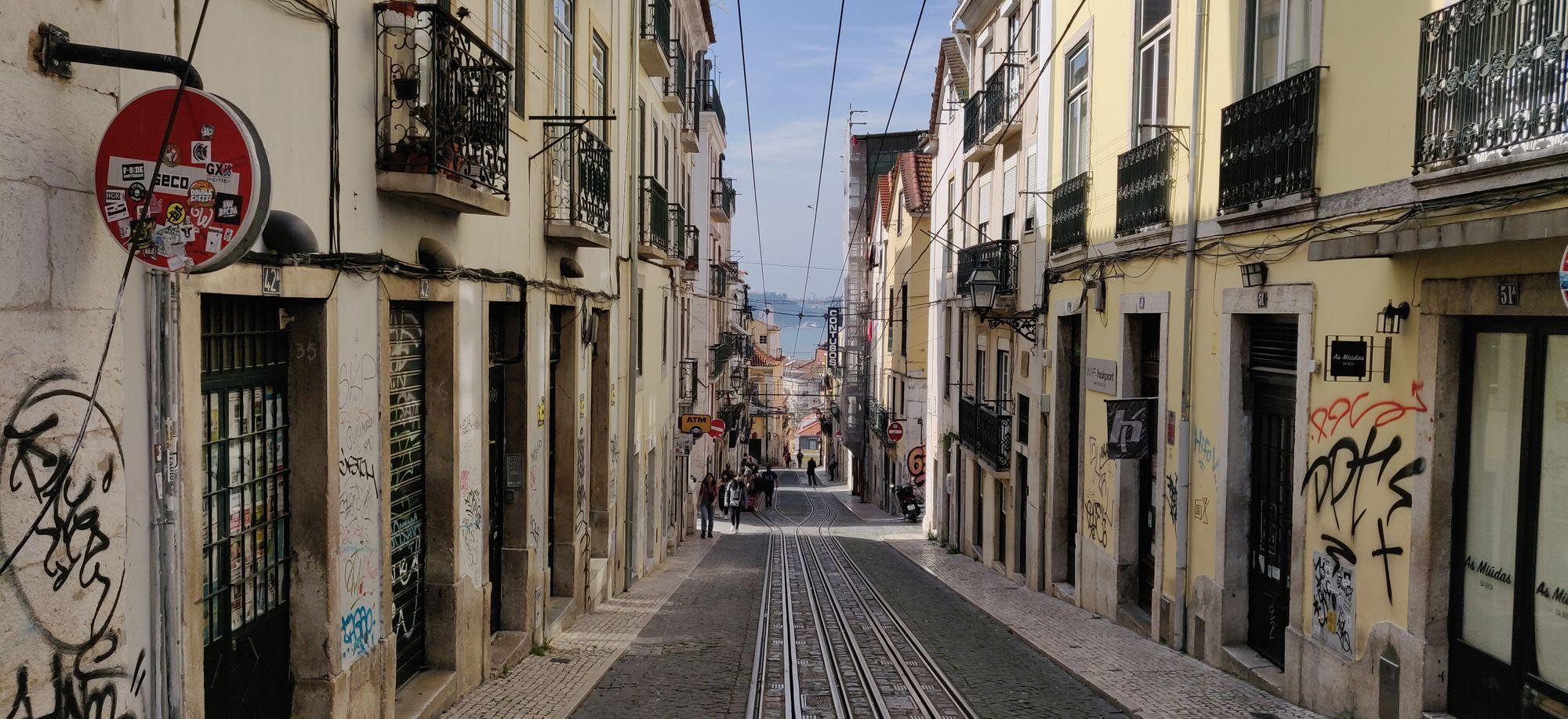 La descente d'une rue avec deux lignes de tramway sur les pavés