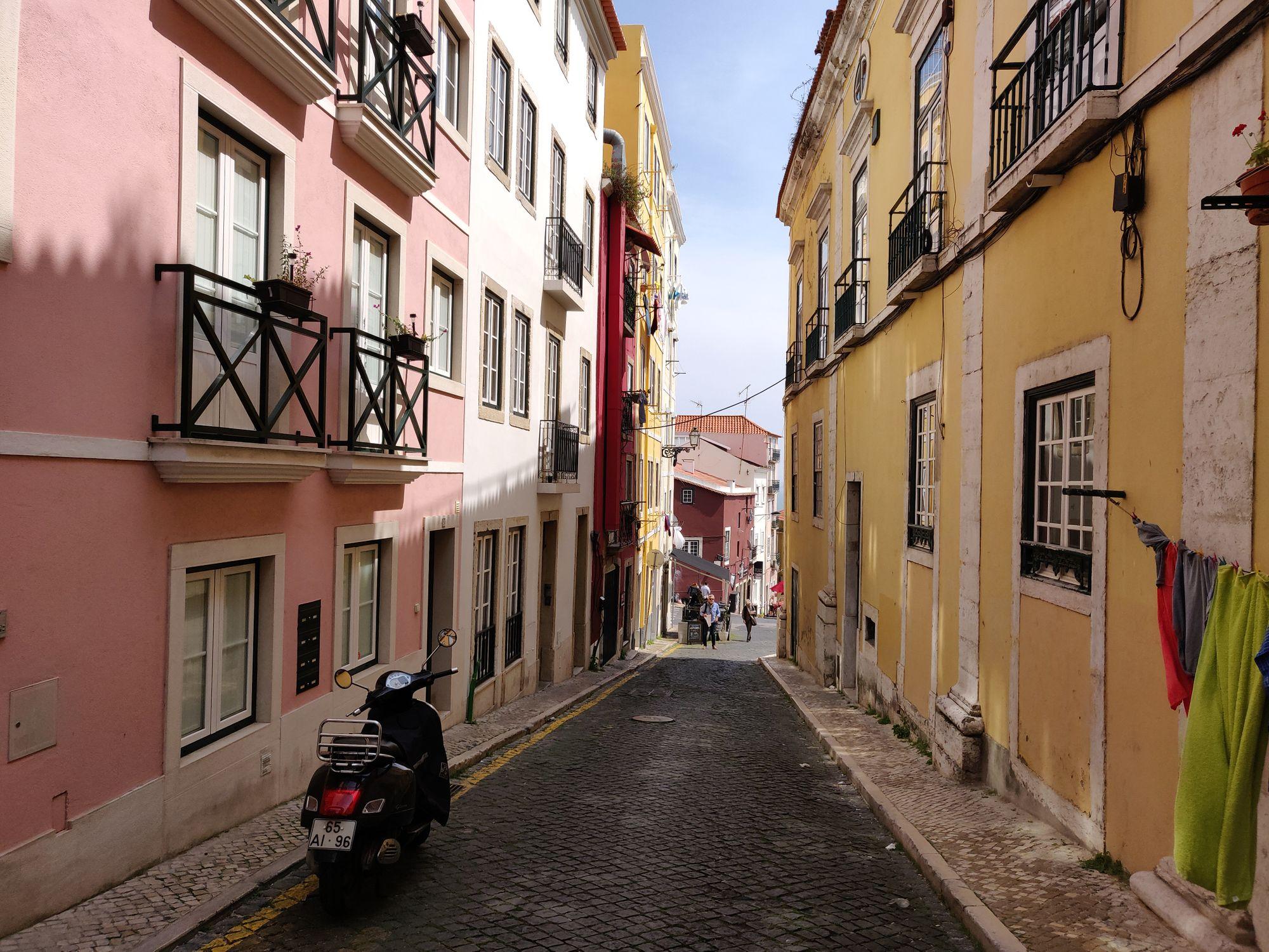 Une petite rue pavé avec des immeubles jaune, rouge, rose et blanc